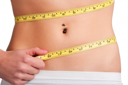 slim tummy: Woman measuring her waist with a yellow measuring tape