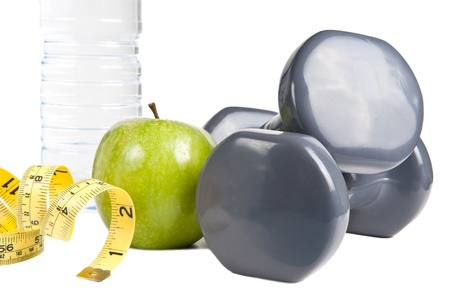 Pair of dumbbells, green apple, measuring tape and bottle of water. Exercise and healthy diet concept. Imagens