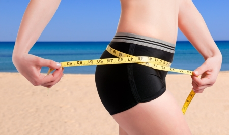 loss: Woman measuring her waist with a yellow measuring tape. Beach background. Stock Photo