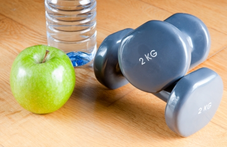 Pair of dumbbells, green apple, measuring tape and bottle of water. Exercise and healthy diet concept. photo