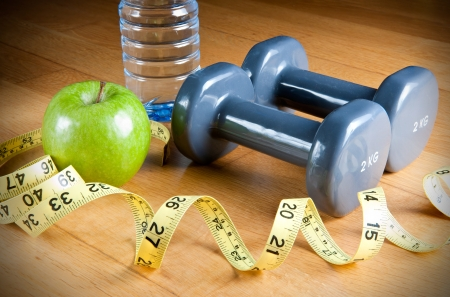 resolutions: Pair of dumbbells, green apple, measuring tape and bottle of water. Exercise and healthy diet concept. Stock Photo