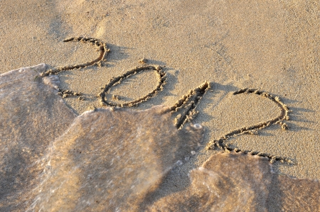 2012 written on sand, being washed out by sea photo