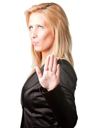 Blond businesswoman shows palm of the hand meaning she's not listening to what's being said