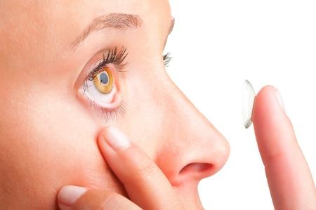 lentes de contacto: Primer plano de una mujer de la inserción de una lente de contacto en el ojo