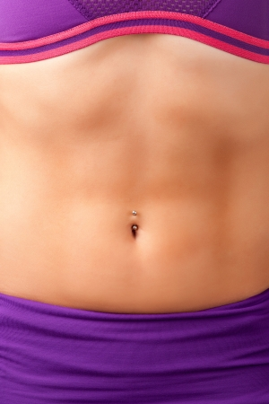 Closeup of a fit womans abs with a pierced belly button photo