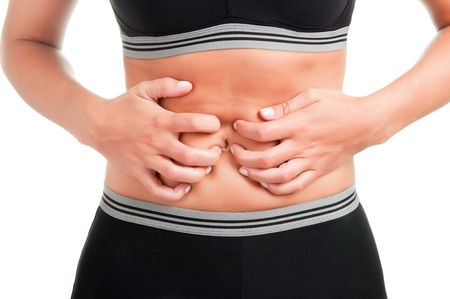 Woman suffering from stomach pain, isolated in white, strong backlight