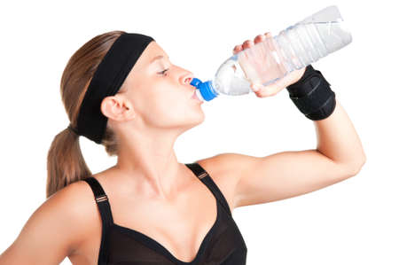 Woman drinking water from a plastic bottle, isolated in white photo