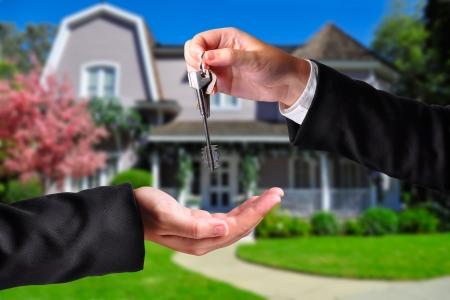 Een hand die een sleutel aan een andere hand. Beide personen in pak en een huis op de achtergrond. Stockfoto