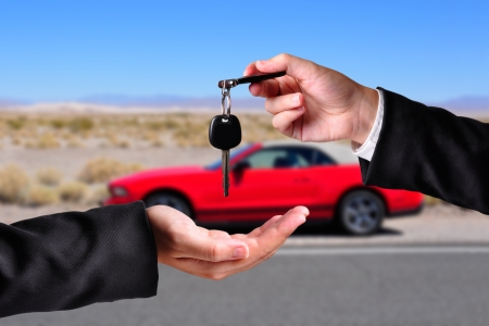 passing over: A hand giving a key to another hand. Both persons in suits. Car in the background. Stock Photo