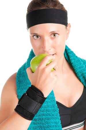 Woman about to eat a green apple after her workout at the gym photo