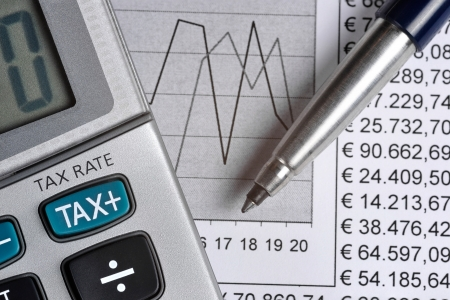 Detail of calculator, focusing the TAX key, next to a sheet of paper with numbers and a metal pen