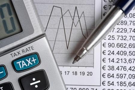 Detail van de rekenmachine, het richten van de TAX-toets, naast een vel papier met nummers en een metalen pen