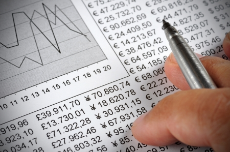 accounts payable: Mans hand holding a pen on top of a document with numbers and a chart Stock Photo