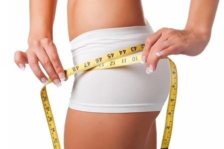 cintas metricas: Mujer que mide su cintura con una cinta métrica amarilla
