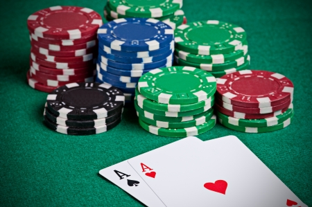 Pair of aces on a poker table with poker chips next to them photo