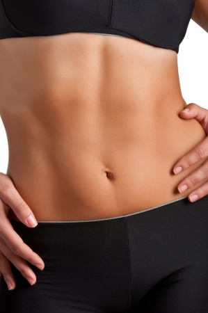 six pack abs: Closeup of a fit womans abs isolated on a white background