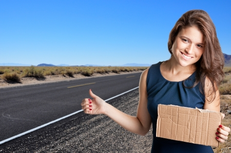 Young woman hitch hiking at a desert road holding a cardboard photo