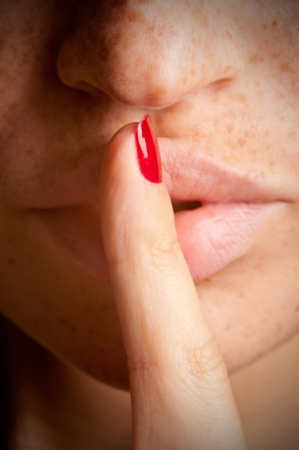 hushed: Closeup of a woman with her finger over her mouth