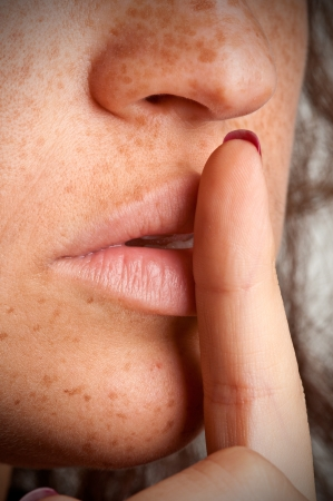 sense of security: Closeup of a woman with her finger over her mouth