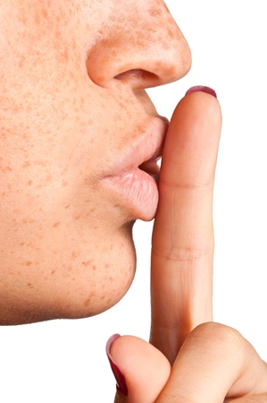 Closeup of a woman with her finger over her mouth photo