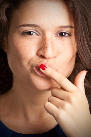 Close-up van een jonge vrouw met haar vinger in haar mond Stockfoto