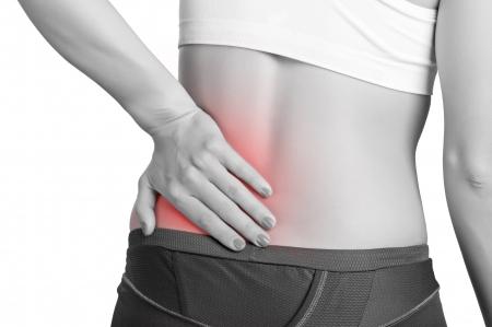 detras de: Mujer joven con dolor en la espalda baja