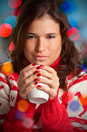 Young woman drinking a hot drink from a white mug Stock Photo - 16590974