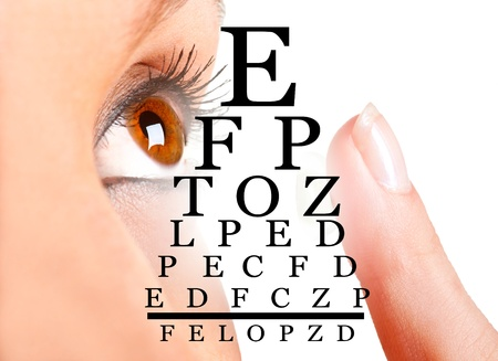 Closeup of a woman inserting a contact lens in her eye 写真素材