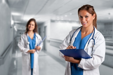 Female doctor writing in a notepad inside an hospital. Another female doctor is in the background. Stock Photo - 16714002