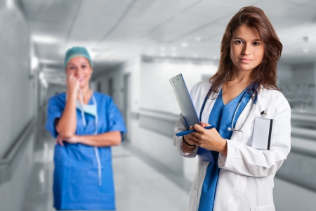 Female doctor writing in a notepad inside an hospital. Another female doctor is in the background. Stock Photo - 16714004