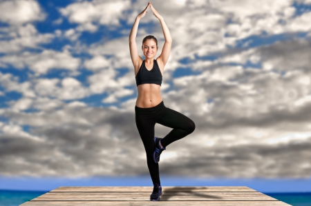 enlightment: Woman practicing  yoga at the beach with clouds behind her