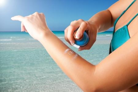 Femme appliquant la crème solaire sur son bras sur une plage Banque d'images