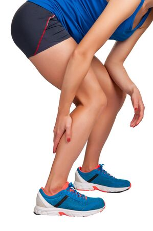 leg injury: Female jogger with pain in her lower leg, isolated in white