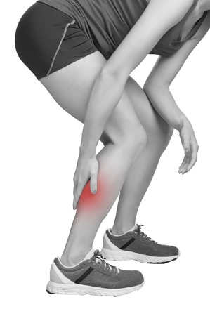 cramped: Female jogger with pain in her lower leg, black and white, isolated in white Stock Photo