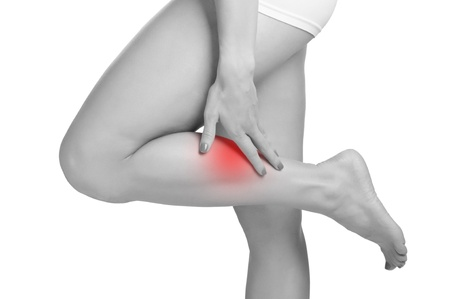 aching muscles: Female with pain in her lower leg, isolated in white Stock Photo