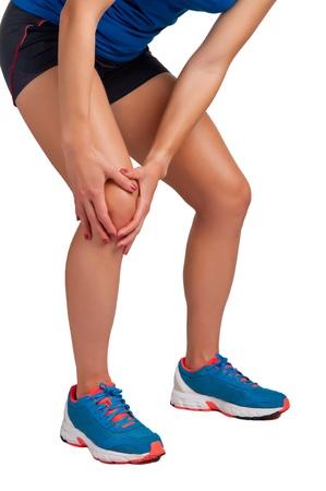 dolor de rodilla: Mujer joven con dolor en su rodilla, aislado en blanco