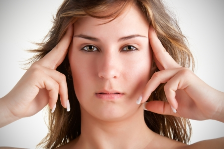 Woman suffering from an headache, holding her hands to the head photo