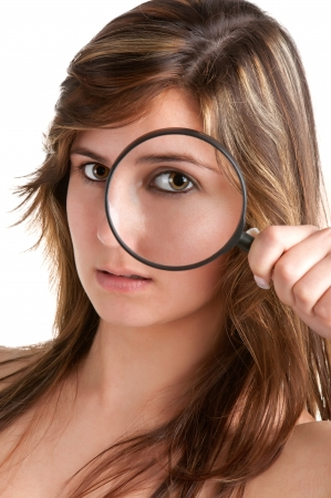 spy girl: Woman looking trough a magnifying glass, isolated in a white background