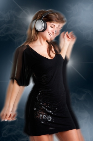 euphoria: Woman dancing using headphones in a dark background, with motion blur Stock Photo