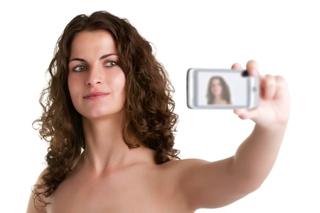 Young woman taking a picture of herself with a cell phone, isolated in a white background photo