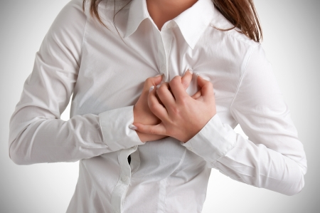 Woman having a pain in the heart area Stockfoto