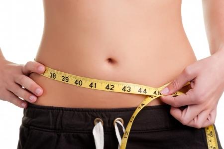 흰색에 고립 된 노란색 측정 테이프와 그녀의 허리를 측정하는 여자