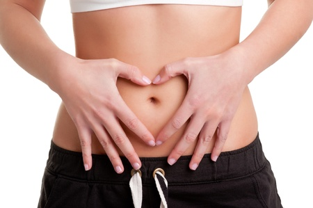 Woman making a heart symbol over her tummy with her hands, isolated in white Stock Photo