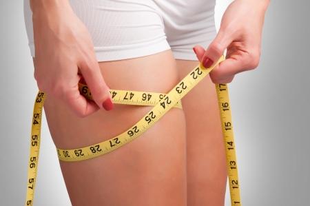 노란색 측정 테이프와 그녀의 허벅지를 측정하는 여자 스톡 사진