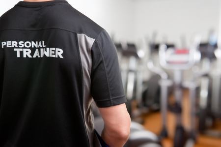 Personal Trainer, with his back facing the camera, looking at a gym Stock Photo