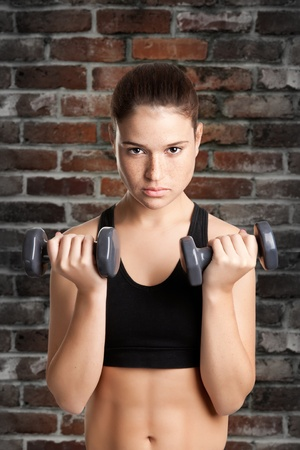 Woman working out with dumbbells at a gym photo