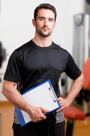 Personal Trainer, met een kussen in zijn hand, in een sportschool Stockfoto