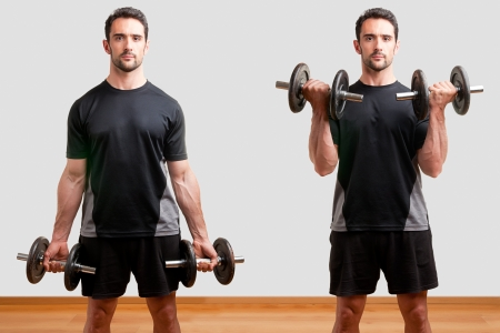 bicep: Personal Trainer doing standing dumbbell curls for training his biceps