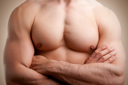 powerful man: Close up of a muscular male torso, arms crossed