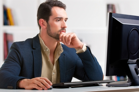 usando computadora: Hombre que mira la pantalla de un ordenador, pensando en el trabajo a mano Foto de archivo